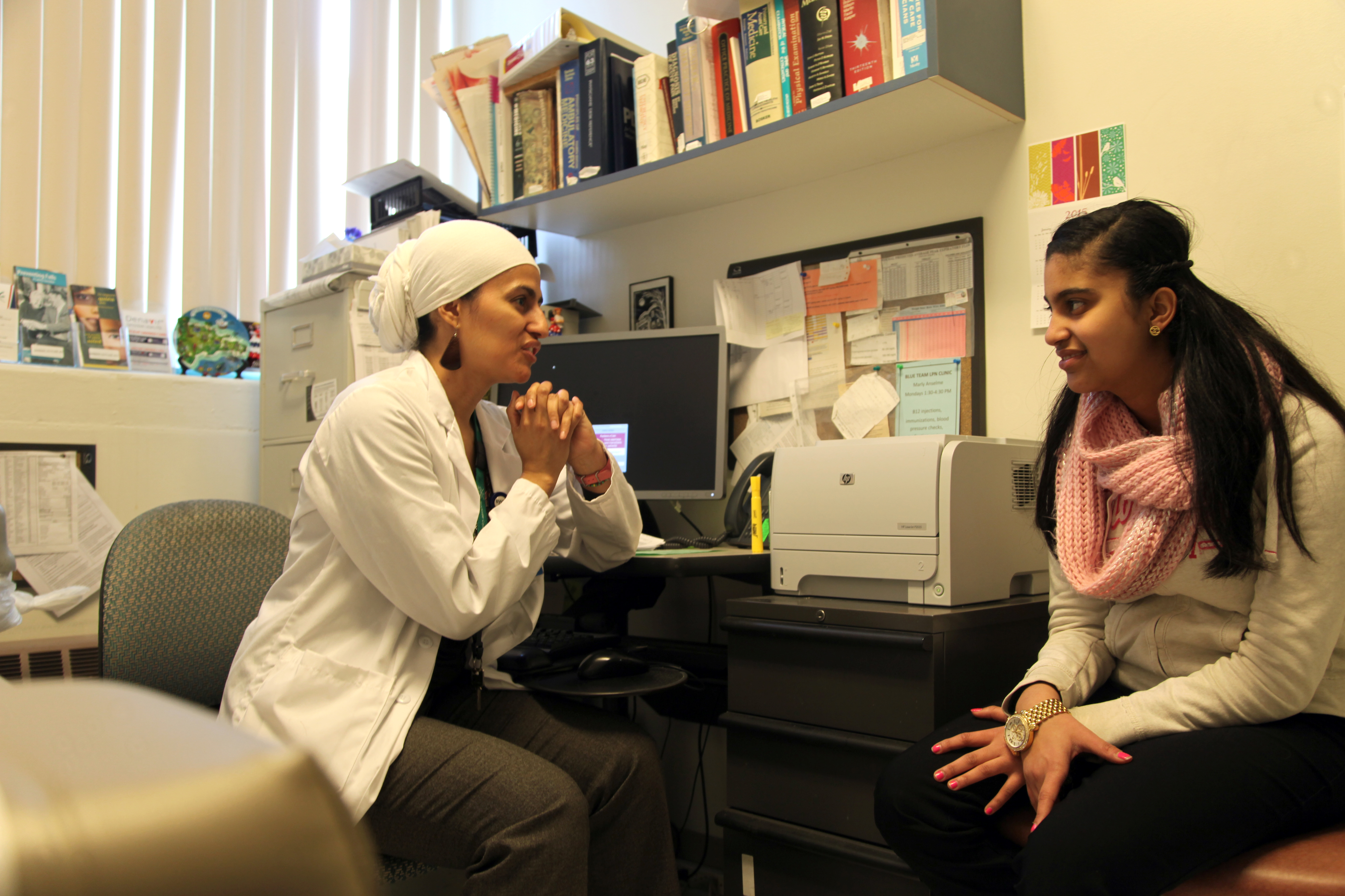Alicia Martinez Beltran, a licensed practical nurse at Brookside Community Health Center, meets with English High student Diana Cabreja.