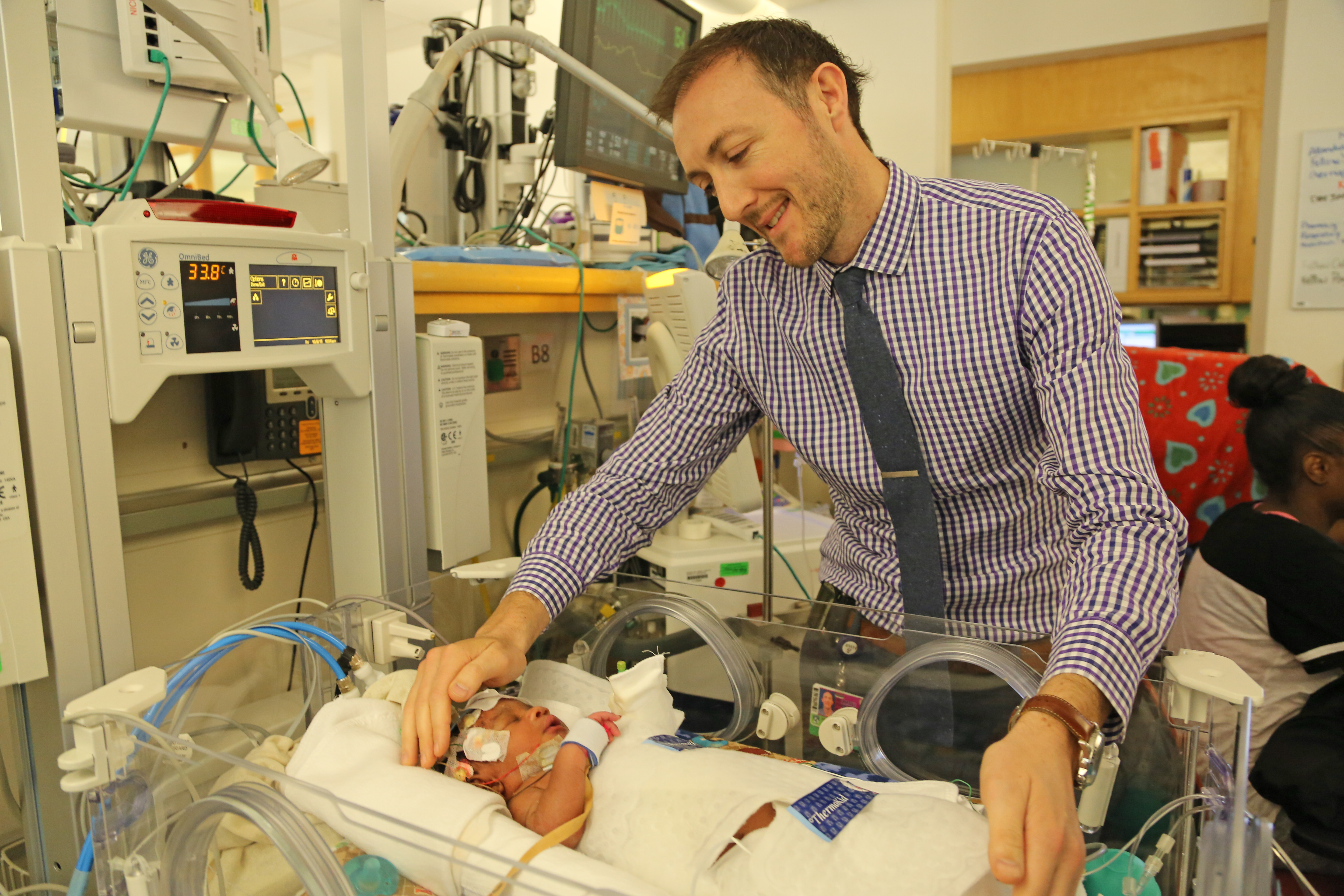 BWH NICU Medical Director Michael Prendergast cares for a baby who is wrapped in a cooling blanket.