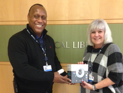 United Way committee member Earl Strong presents campaign donor Judy Walls, of BWH's Medical Library, with a raffle prize.