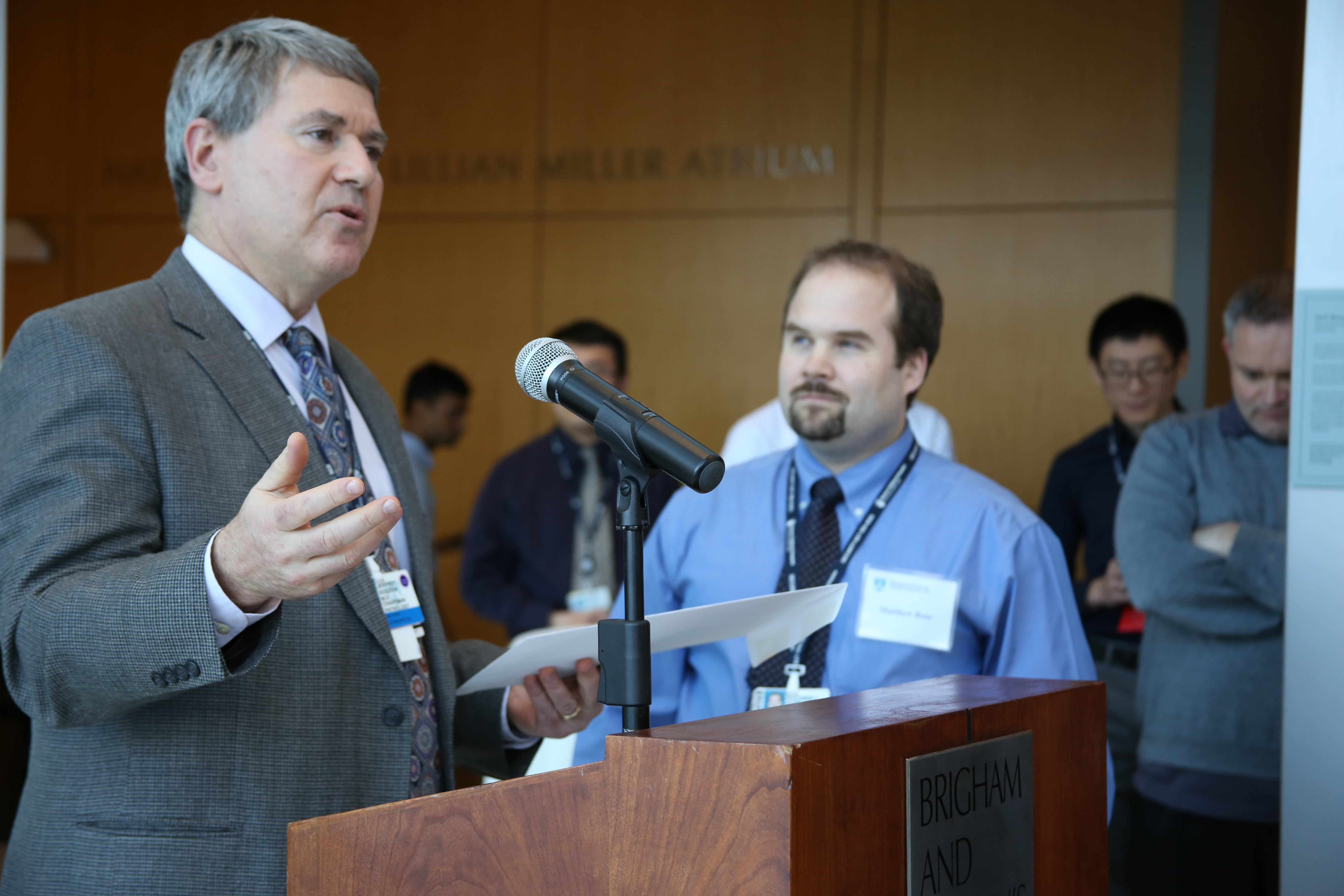 Jeffrey Golden, left, announces the award winners, including Matthew Rose, right, at the Department of Pathology's annual research celebration.