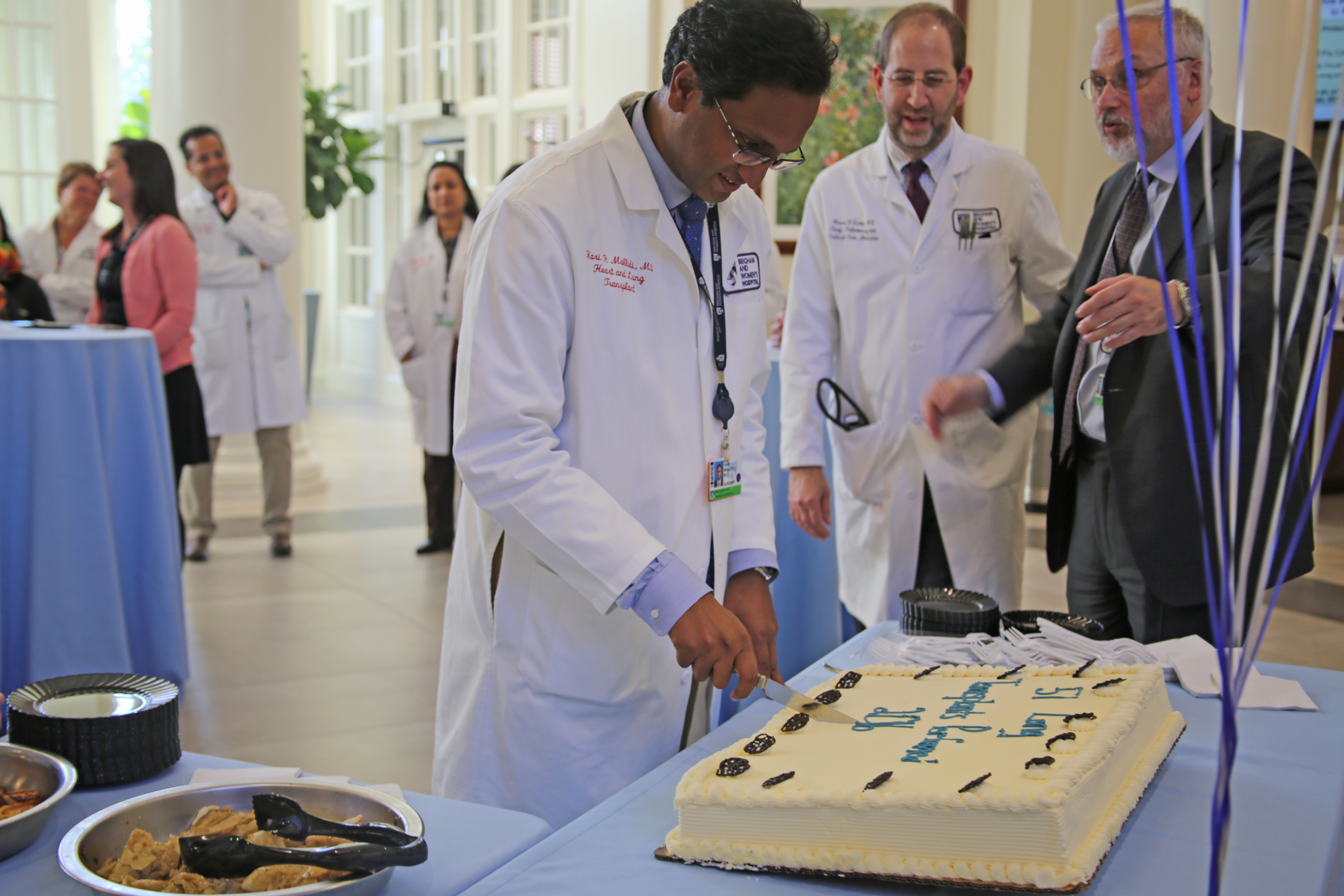 From left: Hari Mallidi cuts a cake celebrating a lung transplant milestone at BWH with Lung Center colleagues Bruce Levy and Raphael Bueno.