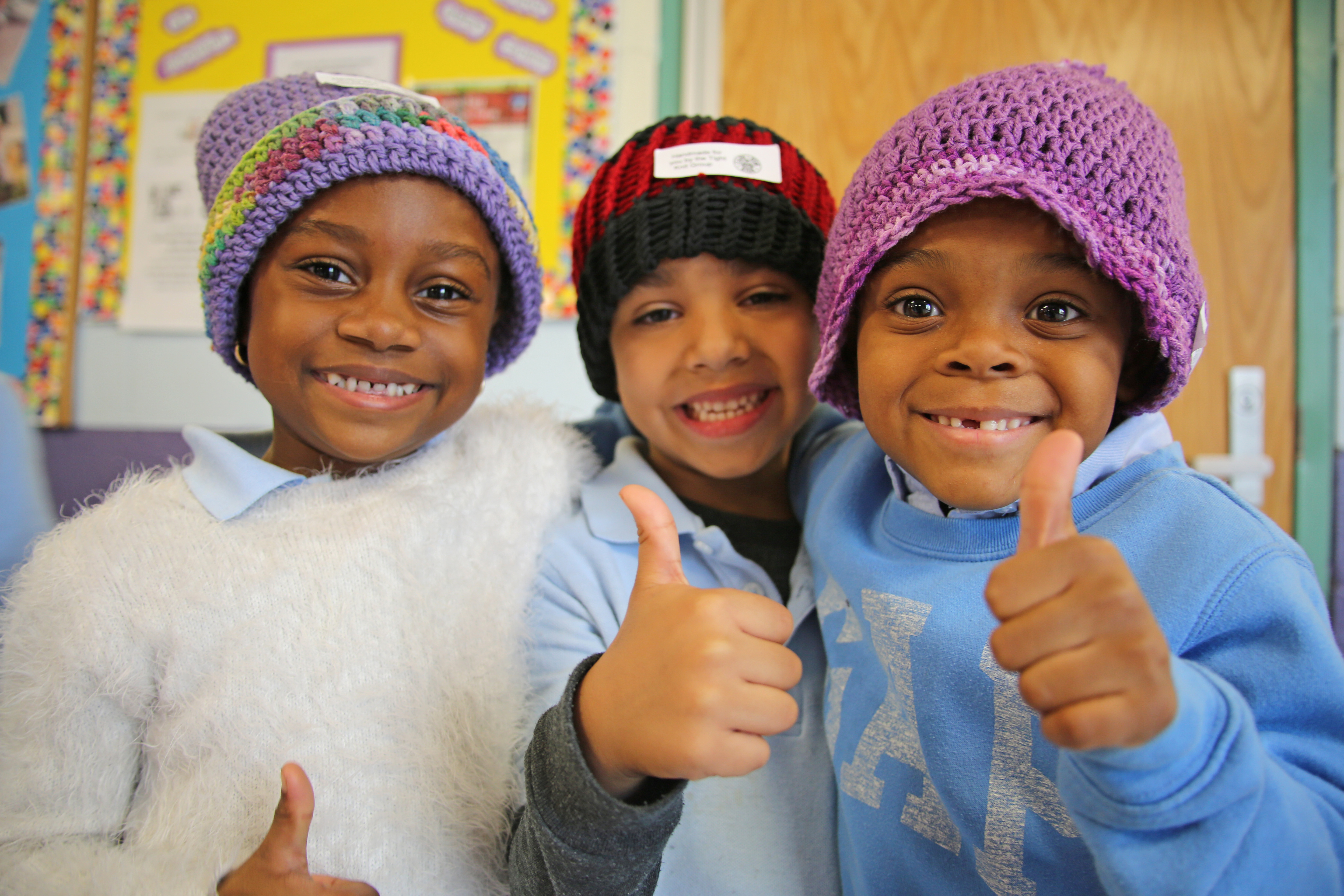 Students from Tobin Elementary School in Mission Hill try on knitted hats donated this year by volunteers at BWH and beyond.