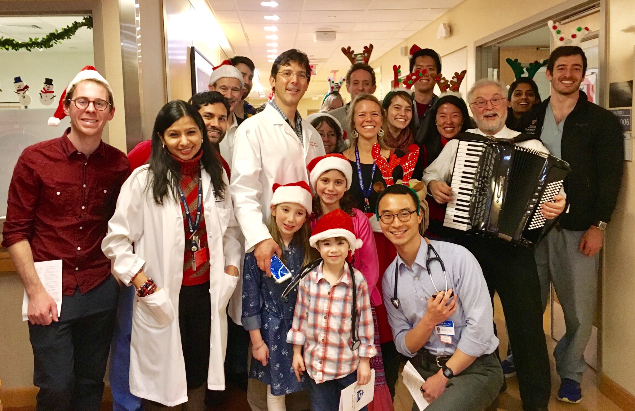 BWHers and their family members gather for a photo after performing holiday carols for patients on Christmas Day.
