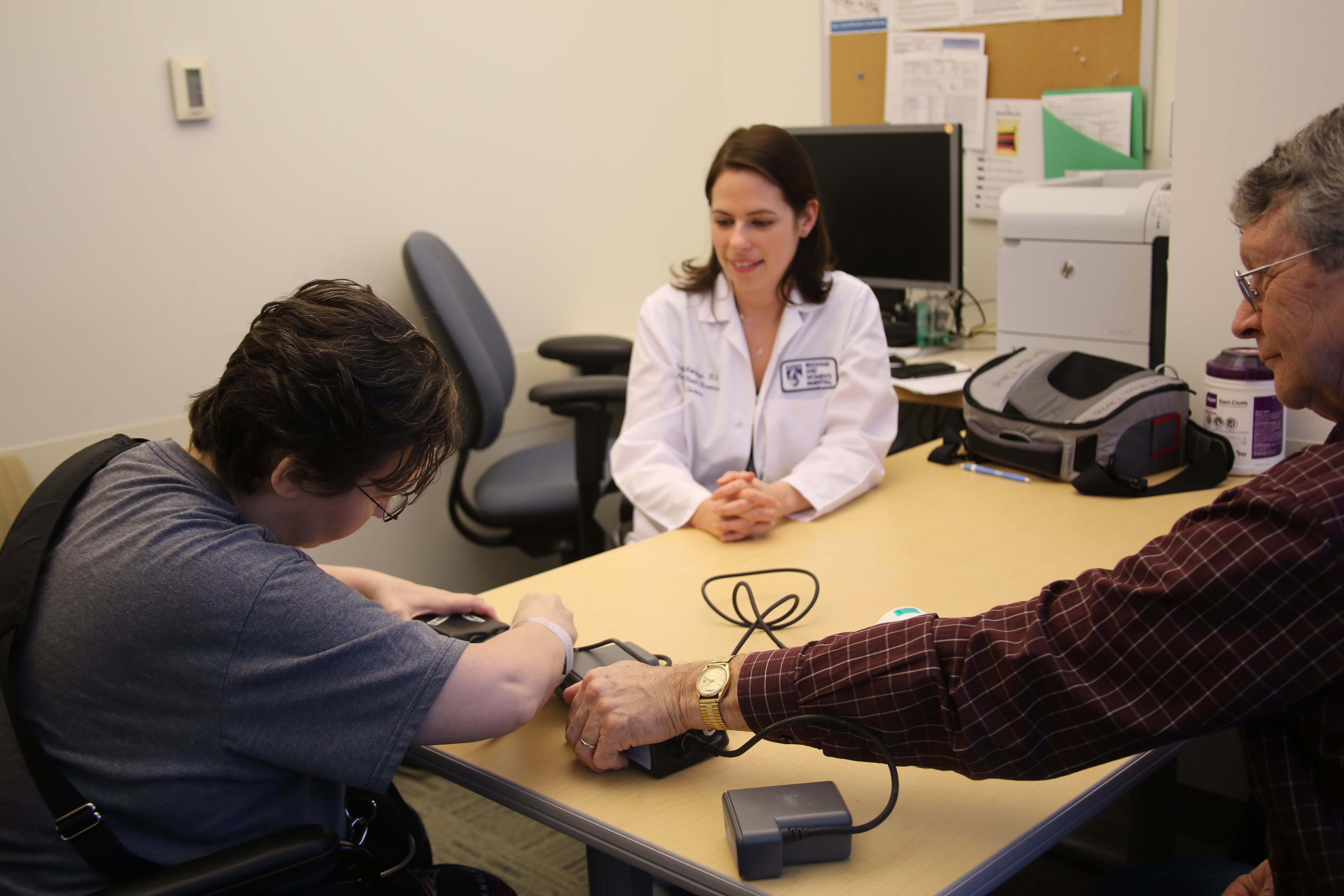 From left: Patient Amy Prince practices hooking up a backup VAD device, with help from BWH nurse Krysten Montoya and Amy's father, Don Prince.