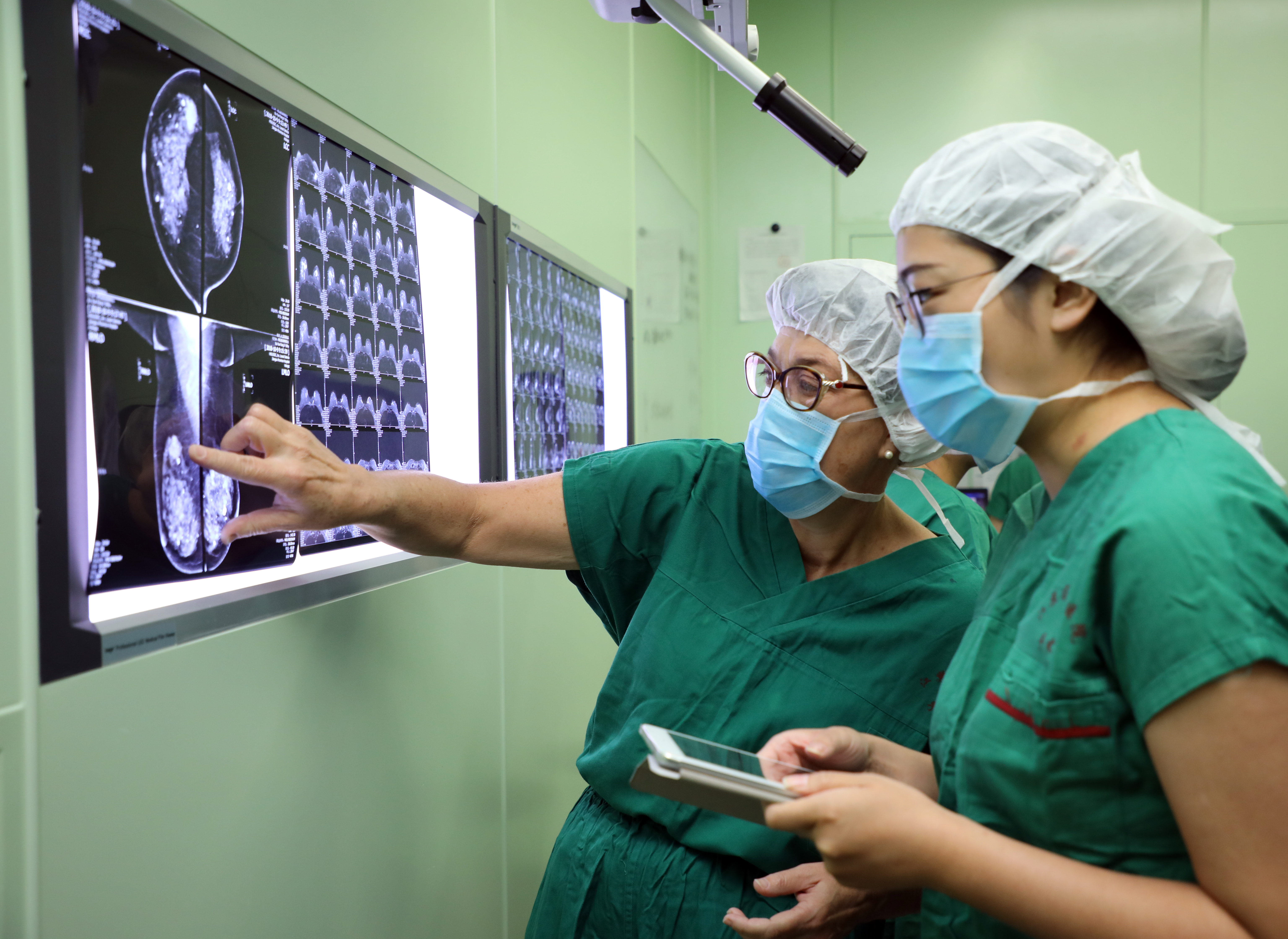Peggy Duggan and a colleague from Jiangsu Province Hospital review a mammogram prior to a procedure there.