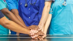 Multiracial team of young doctors stacking hands indoor, Group Of Multiracial Doctor surgery team stacking hands in a operating room, medical teamwork