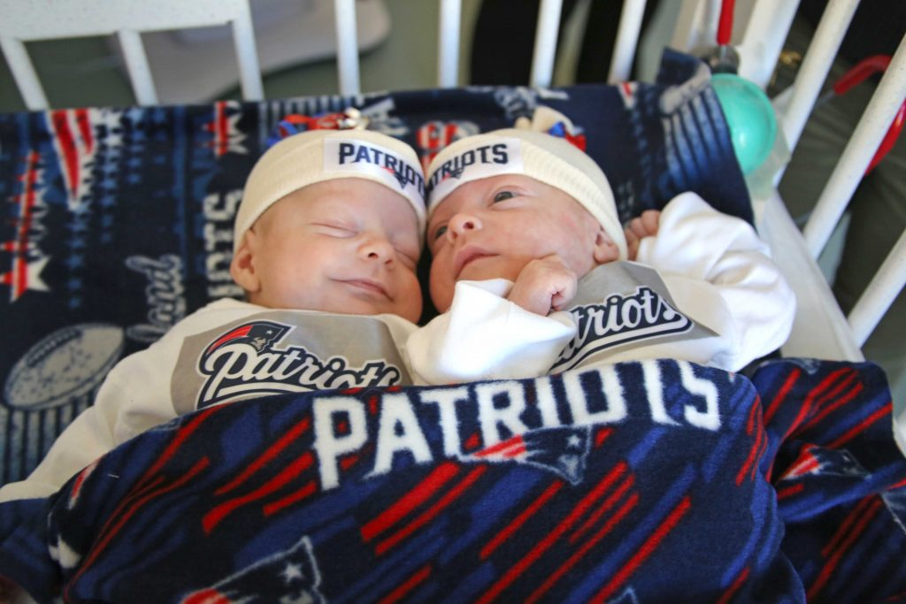 Benjamin and Samuel snuggle in their Patriots gear.