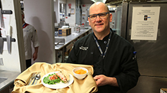 Richard Duclos displays a meal featuring locally sourced kale pesto and squash.