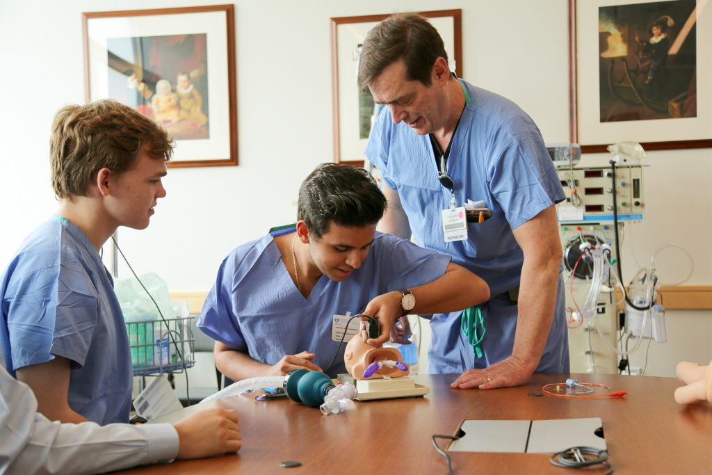 Nick Chehwan (center) practices intubation using a simulation device, with guidance from David Beadles (right).