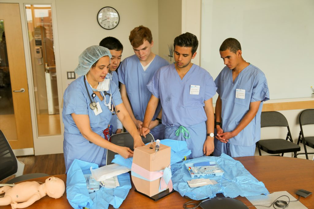 From left: Michaela Farber simulates an epidural injection for Christopher Zhu, Ian Richardson, Nick Chehwan and John Harrington