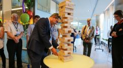 Paul Anderson (center) prepares to remove a Jenga piece from a large- scale version of the game, one of several festivities at the event.