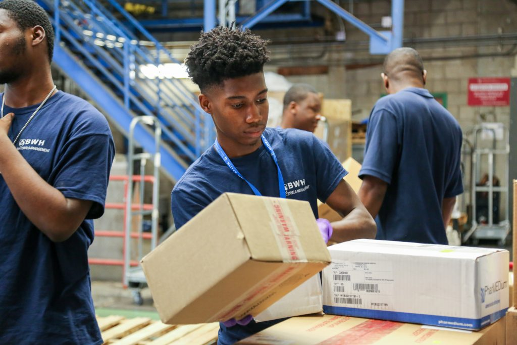 Stevenson Elianor organizes incoming packages at the Central Receiving loading dock.
