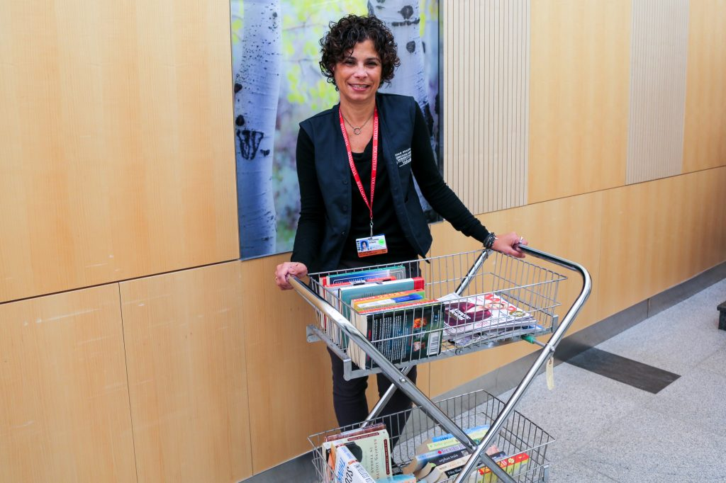 Suzanne Erwin standing with book cart