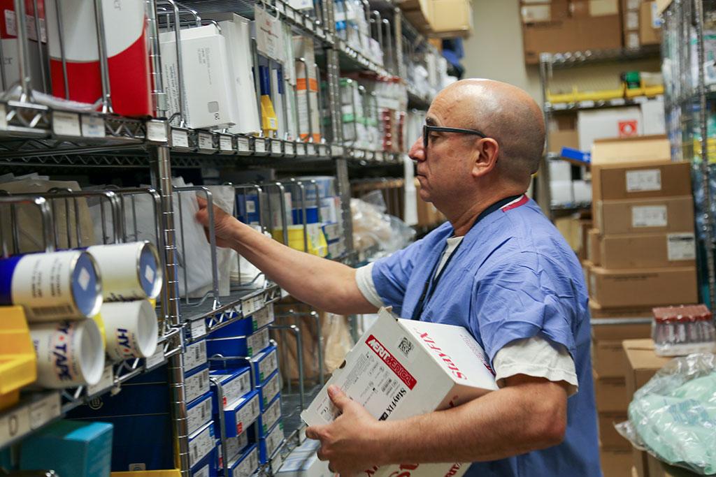 Mustapha Khiyaty examining shelves with supplies