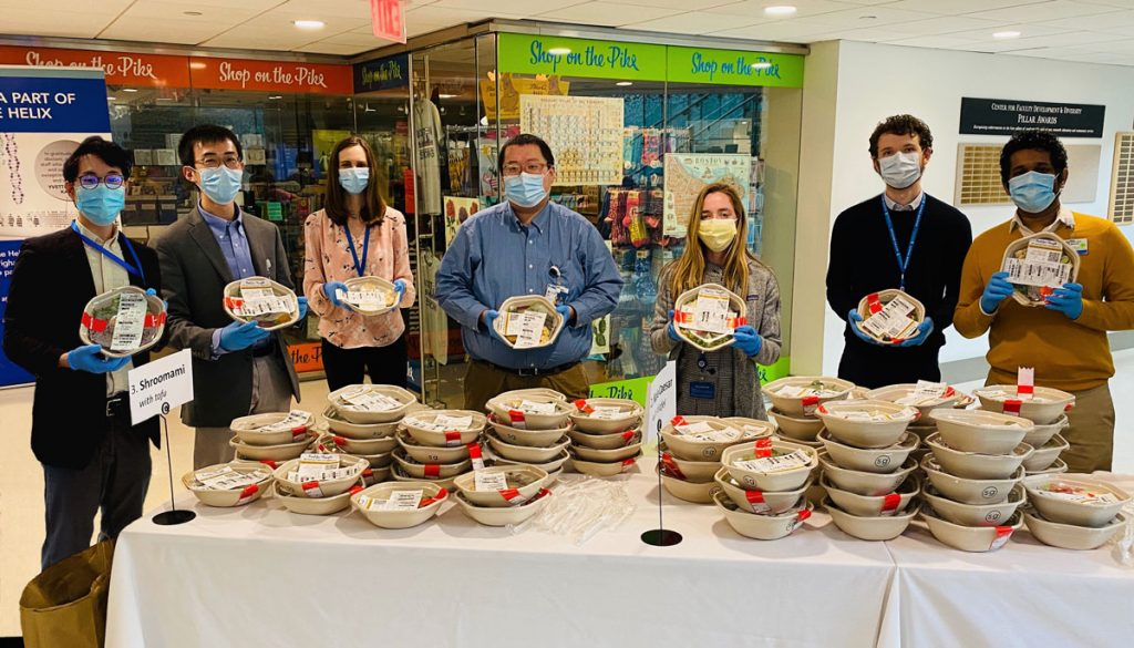 Masked people distributing food at hospital