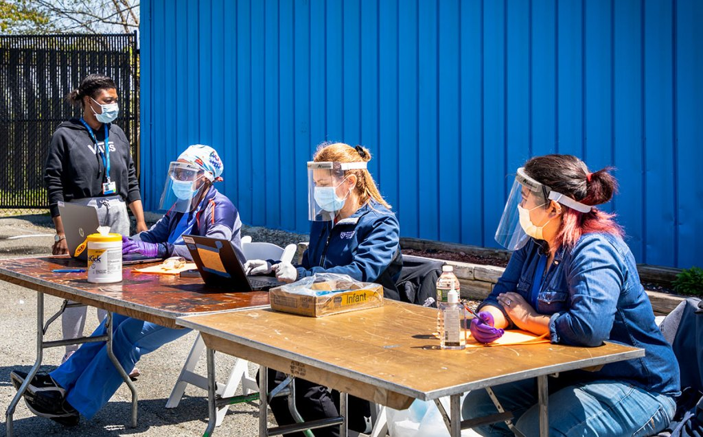 people sitting at table in masks